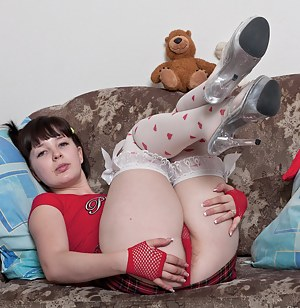 Candy S loves how sexy she looks in her red outfit with gloves and polka dot stockings. She lays around the loveseat and strips. Then she plays with her tits, but likes her hairy pussy more!