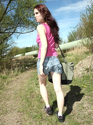 Horny daring teenager strokes pussy outside in the grass