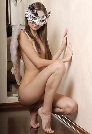 An alluring blonde with angels wings on her back and a mask on her cute face posing naked in her apartment