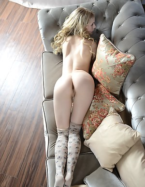 Curly haired blonde babe showing her beauty through her tight pussy and sexy glare while she poses with passion.