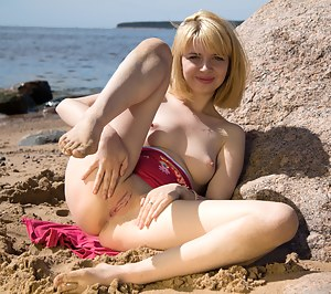Horny coed plays with her tiny tits and tight pussy on the beach